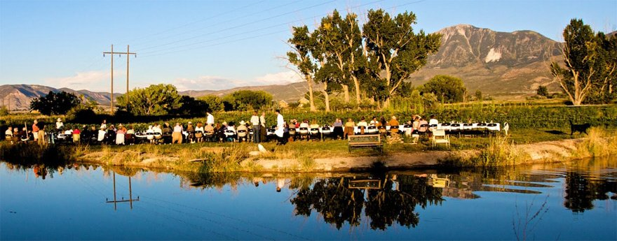 People gather around a dinner table with Mt Lamborn in the background for a farm-to-table dinner in Paonia.